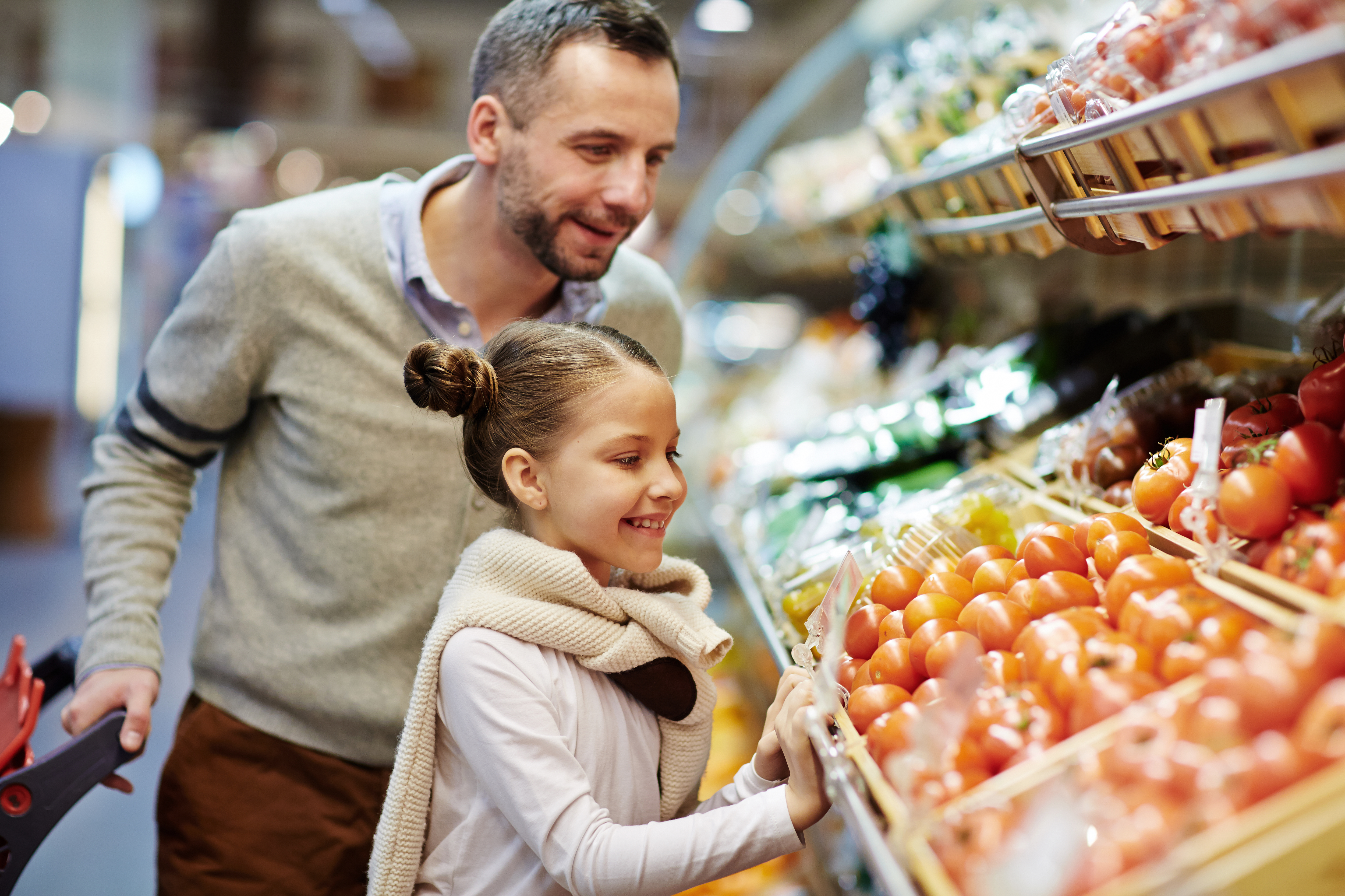 Portrait of cute little girl with dad leaning over vegetable counter choosing fresh ripe tomatoes and other vegetables at FNGs.